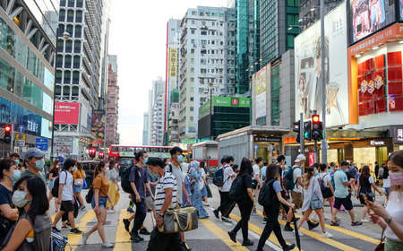 Hong Kong - May 24, 2020: Street view in Mongkok district. People walking on the street and wearing mask to protect corona virus spread in air. Mongkok is one of the major shopping area in Hong Kong. Redactioneel