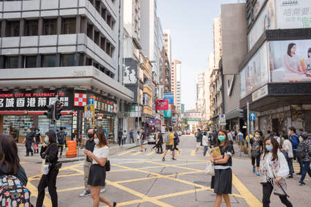 Hong Kong - April 27, 2020: Street view in Tsim Sha Tsui. People walking on the street and wearing mask to protect corona virus spread in air.Tsim Sha Tsui is a center of various shopping places Banco de Imagens - 154374524