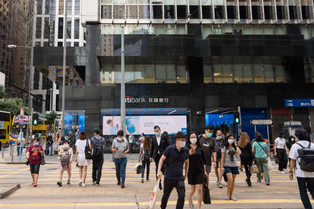 Hong Kong - August 24, 2020: Street view in Central district. People walking on the street and wearing mask to protect corona virus spread in air. Central area is main commercial district of Hong Kong