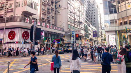 Hong Kong - November 19, 2020: Street view in Tsim Sha Tsui. People walking on the street and wearing masks to protect coronavirus spread in air. Tsim Sha Tsui is a center of various shopping places Banco de Imagens - 159414558