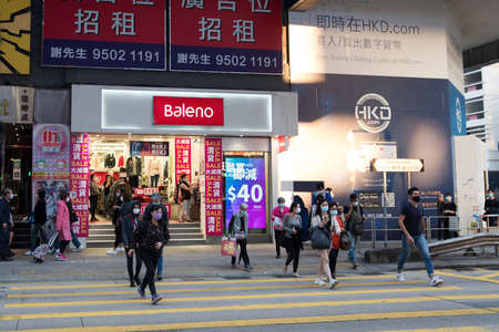 Hong Kong - December 01, 2020: Street view in Mongkok. People walking on the street and wearing masks to protect coronavirus spread in the air. Mongkok is one of the major shopping areas in Hong Kong.