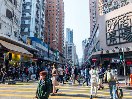 Hong Kong - March 26, 2021: Street view in Mongkok. People walking on the street and wearing masks to protect coronavirus spread in the air. Mongkok is one of the major shopping areas in Hong Kong.