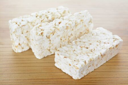 Three rice craker bars on wooden table