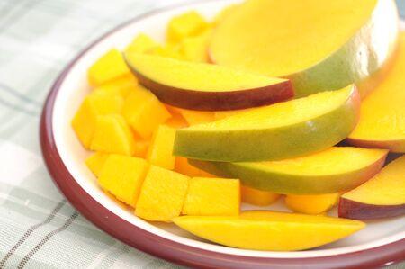fresh and juicy slice of mango on dish on napkin