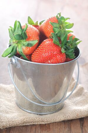 a pail of fresh strawberry on the table Stock Photo