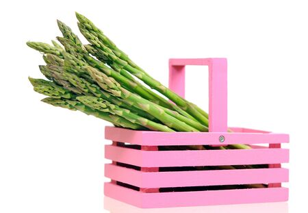 fresh asparagus in pink bucket on white at market place