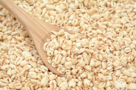 sweet popped rice on wooden spoon for background uses