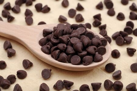 dark and sweet chocolate chips in wooden spoon Stockfoto
