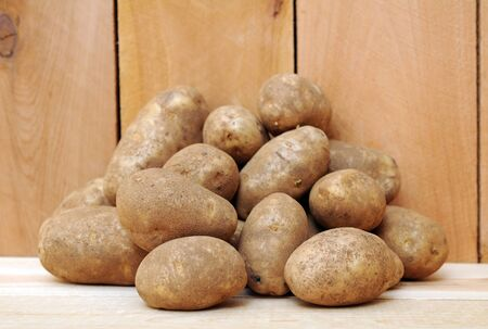 a pile of russet potatoes on wooden shelf Stock Photo