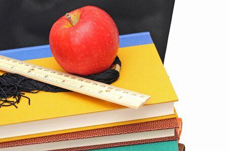 many books , ruler, apple and graduated cap