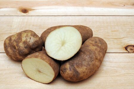 cutting and whole russet potatoes on wooden shelf