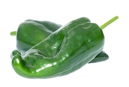 two organic poblano peppers isolated on white background