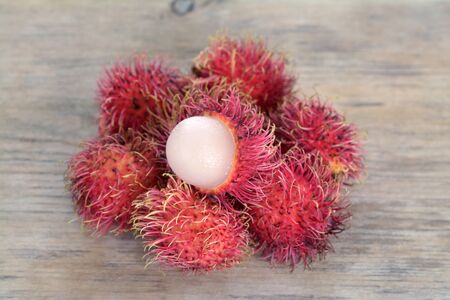 a pile of rambutan fruit  on wooden table Stock Photo