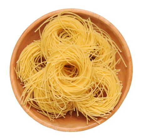 bunches of nested noodle pasta in wooden bowl isolated on white background