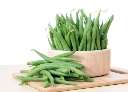 green beans in wooden bowl on white background