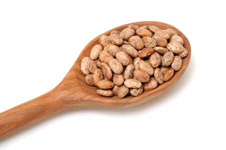 pinto bean on wooden spoon on white