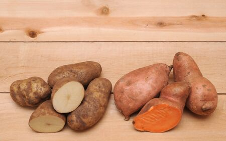 sweet and russet potatoes on wooden table Stock Photo