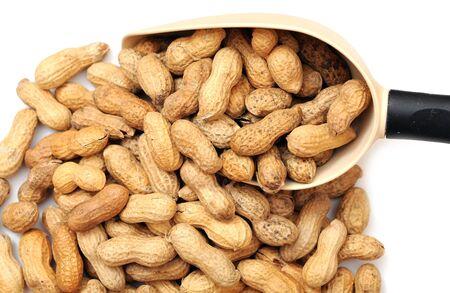 große Schaufel und getrocknete Erdnuss auf weißem Hintergrund
