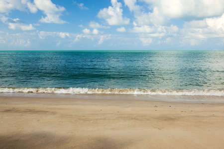 over the horizon: Empty tropical ocean beach with clouds over water