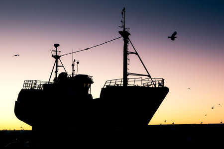 Fishing vessel silhouette at sunset in port, Essaouira, Morocco photo