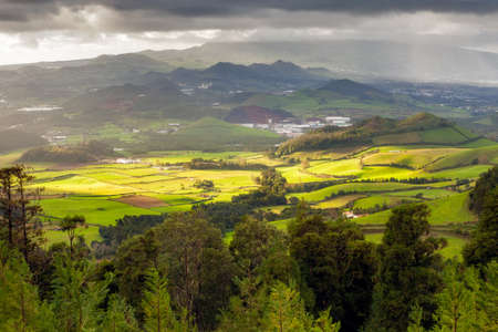 simultaneously: Aerial view to fields of San Miguel island under heavy rain and sun simultaneously, Azores, Portugal