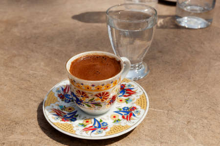 Trditionally served turkish coffee at the street cafe under light sun, Istanbul, Turkey photo