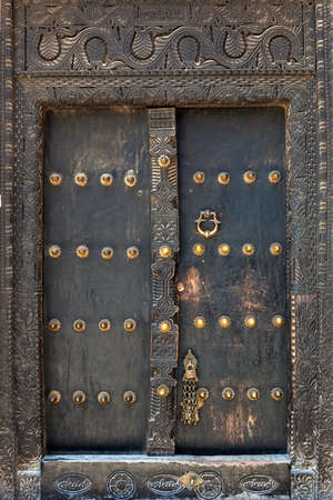 Old weathered door of building in Stone Town, Zanzibar, Tanzania photo