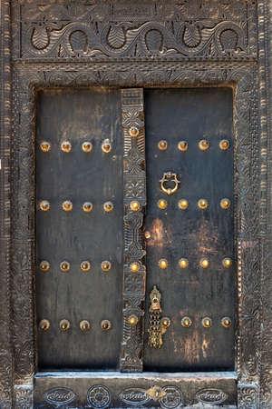 wood carving door: Old weathered door of building in Stone Town, Zanzibar, Tanzania