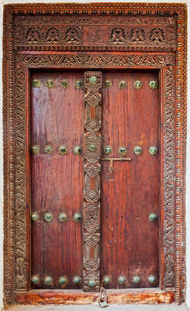 Old weathered carved traditional door of building in Stone Town, Zanzibar, Tanzania photo