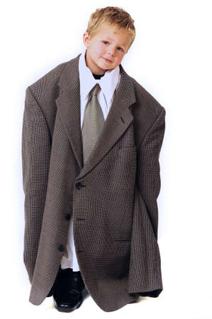 Blond young Boy in oversized business clothes standing photo