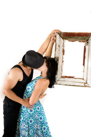 sexy pictures: Young in love couple kissing behind a hat leaning against a suspended frame