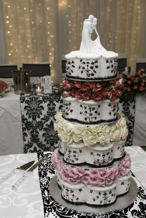 icing: Multi layered wedding cake with bridal figurines and fairy lights Stock Photo