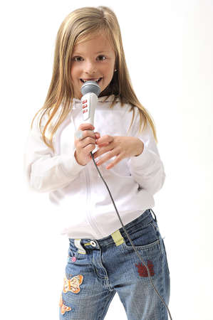 kareoke: young pretty blond girl singing using a microphone in studio Stock Photo