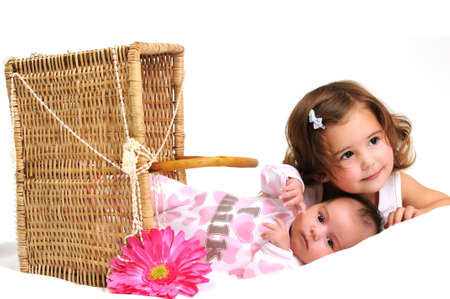 two sisters playing and smiling in a basket with pink flower Stock Photo - 7987478