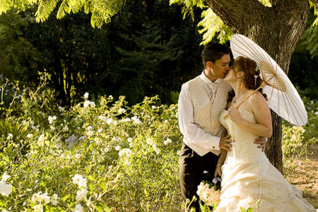 passionate kissing: just married couple standing and kissing in white flower bed under a tree in nature on a sunny day Stock Photo