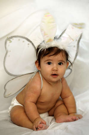 alice band: cute baby sitting and smiling with angel wings and colorful bunny ears Stock Photo