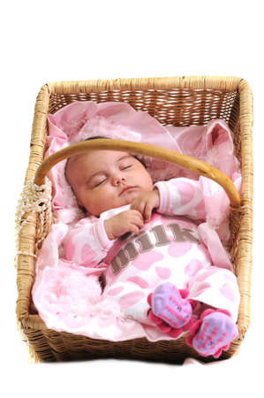 baby girl in pink dots laying in a brown basket draped with white beads photo