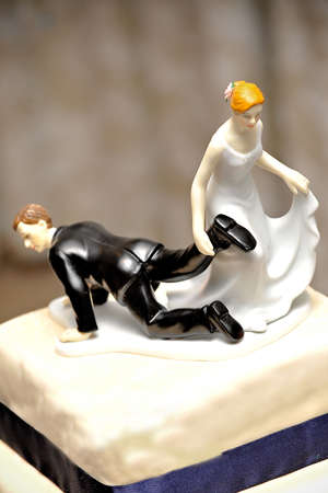 figurines: wedding figurine on cake with bride dragging the groom doll by the feet to the church symbolically