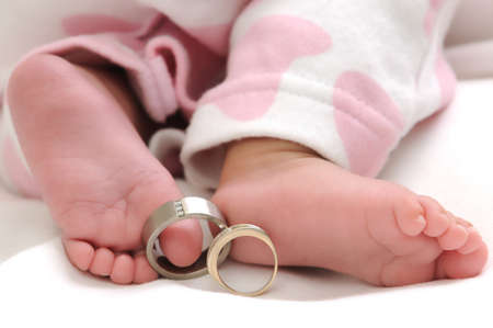 wedding rings on the toes of a baby girl wearing white and pink clothes photo