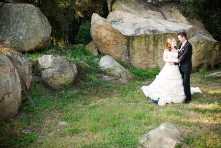 red head sexy beautiful bride in white and groom hugging and standing outside in sun next to boulders of rocks on green grass photo