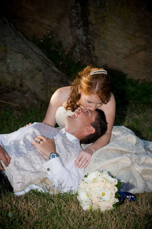 red head sexy beautiful bride in white and groom hugging and sitting outside next to boulders of rocks on green grass photo