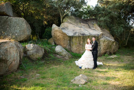 red head sexy beautiful bride in white and groom hugging and standing outside in sun next to boulders of rocks on green grass Stock Photo - 8196021