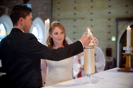 wedding couple lighting the yellow main candle together with their own smaller candles in church during the church ceremony photo
