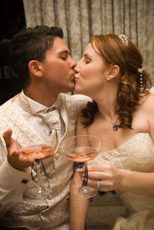 sexy beautiful young bridal couple kissing and holding champagne glasses together Stock Photo - 8196000