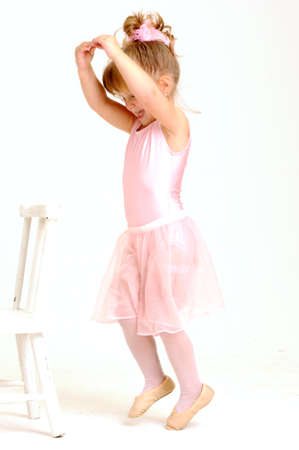 cute little girls: Little smiley girl wearing a pink ballet outfit is dancing holding her dress Stock Photo