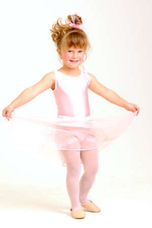 Little smiley girl wearing a pink ballet outfit is dancing holding her dress Stock Photo - 8359801