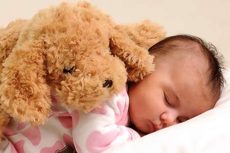animalitos tiernos: beb� con blanco y Rosa ropa para dormir, duerme con el perro de juguete marr�n en su espalda Foto de archivo