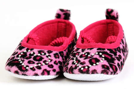a pair of pink and red baby shoes with a crystal heart on photo