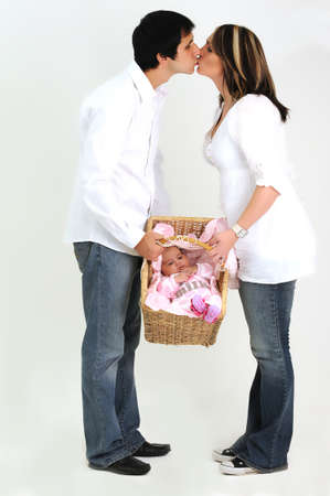 couple holding new baby in basket and kissing photo