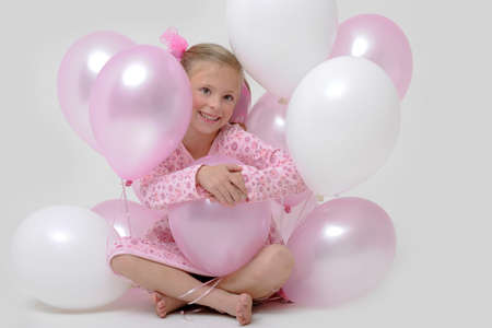 a pretty young blond girl sitting between pink and white balloons photo